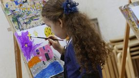 Young cute Female Artist is in an Art Studio, Sitting Behind an Easel and Painting on Canvas. Drawing Process: in the. Young Beautiful Female Artist is in an Art stock video
