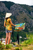 Young beautiful female artist painting Old Kotor, Montenegro, on mountain background Royalty Free Stock Images