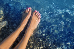 Young and beautiful female bare feet with red painted nails standing on a beach under waves. Royalty Free Stock Photos