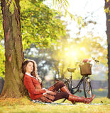 Young beautiful female with bicycle relaxing in a park on a sunn Stock Photo
