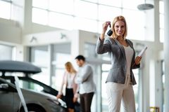 Young female car sales consultant working in showroom royalty free stock image
