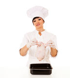 Young beautiful female chef presenting raw chicken Royalty Free Stock Photos
