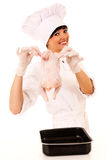 Young beautiful female chef presenting raw chicken Royalty Free Stock Image