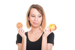 Young beautiful female choose from sweet cake and red apple Royalty Free Stock Photo
