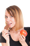 Young beautiful female choose from sweet cake and red apple Stock Photo