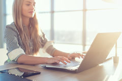 Young beautiful female copywriter typing texts and blogs in spacious light office, her workplace, using pc keyboard. Busy woman working Royalty Free Stock Photo