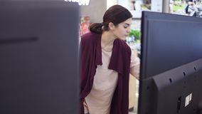 Young beautiful female costumer choosing new TV screen in electronics store. Young beautiful female costumer choosing new TV screen in electronics store stock footage
