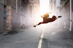 Young and beautiful female dancer in a red dress. Jumping royalty free stock image