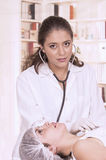 Young beautiful female doctor checking patient Royalty Free Stock Images