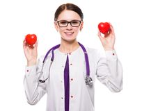 Young beautiful female doctor holding hearts in her hands on white background. Portrait of young attractive positive friendly smiling woman doctor standing in Stock Photography