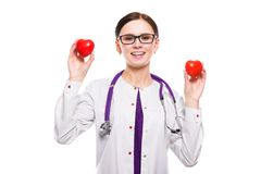 Young beautiful female doctor holding hearts in her hands on white background. Portrait of young attractive positive friendly smiling woman doctor standing in Royalty Free Stock Images