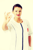Young beautiful female doctor holding pink pill Stock Images