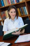 Young and beautiful female doctor in library s. Young and beautiful female doctor in a library s Royalty Free Stock Image