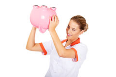 Young beautiful female doctor or nurse holding a piggybank Royalty Free Stock Photography