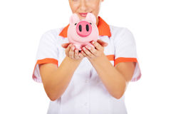 Young beautiful female doctor or nurse holding a piggybank Stock Photos