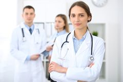 Young beautiful female doctor smiling on the background with patient in hospital stock images