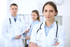 Young beautiful female doctor smiling  on the background with patient  in hospital. High level and quality medical service concept Stock Photography