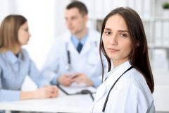 Young beautiful female doctor smiling on the background with patient in hospital stock photos