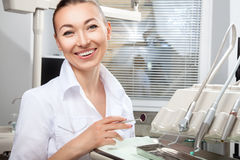 Young beautiful female doctor smiling holding dental mirror Royalty Free Stock Photo
