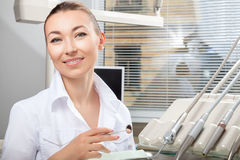Young beautiful female doctor smiling holding dental mirror Royalty Free Stock Images