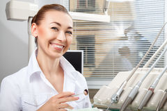 Young beautiful female doctor smiling holding dental mirror Royalty Free Stock Photography