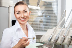 Young beautiful female doctor smiling holding dental mirror Royalty Free Stock Photos