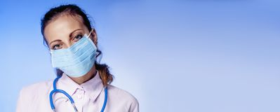 Young beautiful female doctor with stethoscope in protective med