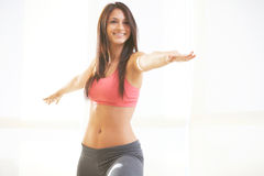 Young beautiful female doing yoga warrior pose Stock Image
