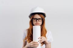 Young beautiful female engineer holding blueprints on white isolated background Stock Image