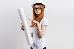 Young beautiful female engineer holding blueprints on white isolated background Royalty Free Stock Images