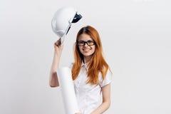 Young beautiful female engineer holding blueprints on white isolated background Stock Photos