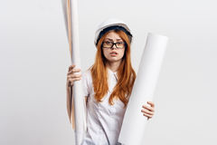 Young beautiful female engineer holding blueprints on white isolated background.  Royalty Free Stock Photography