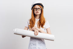 Young beautiful female engineer on white  background holds drawing, construction Stock Photo