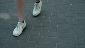 Young beautiful female feet in white sneakers walking on the tile shape rhombus summer on a hot day stock footage
