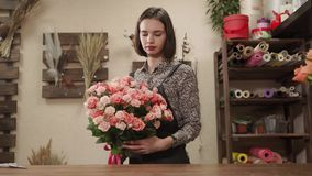 Female florist decorating a bouquet. Young beautiful female florist decorating pink roses bouquet indoor. She is tying a red ribbon to it stock video footage