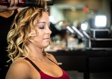 Young Beautiful Female Getting Hair Styled and Curled royalty free stock photography