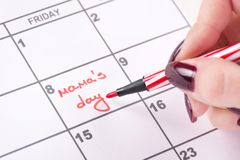 Woman hands with red felt pen writes words Mamas day in calendar stock photos
