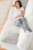 Young beautiful female having a rest on a sofa Royalty Free Stock Images