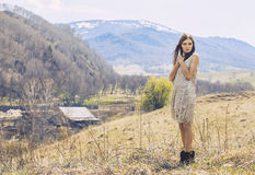 Young beautiful female model in a landscape with mountains and v. Illage, standing on a hill royalty free stock image