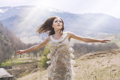 Young beautiful female model in a landscape with mountains and v. Illage, standing on a hill stock photos