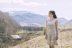 Young beautiful female model in a landscape with mountains and v. Illage, standing on a hill royalty free stock photos