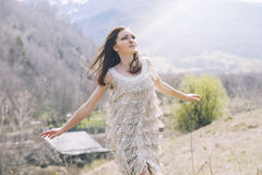 Young beautiful female model in a landscape with mountains and v. Illage, standing on a hill stock photography