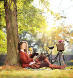 Young beautiful female in park reading a book and eating apple Stock Photography