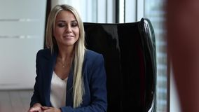 Young beautiful female personnel manager sitting in a chair in an office. Interview stock video