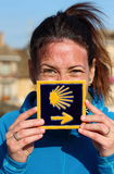 Young beautiful female pilgrim's portrait posing with the typical Camino de Santiago tile Royalty Free Stock Image