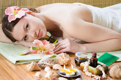 Young girl relaxing in spa salon & flower in hair Royalty Free Stock Photos