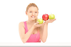 Young beautiful female sitting and holding apples Royalty Free Stock Image