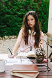 Young beautiful female sitting outside and studying hard. Royalty Free Stock Image