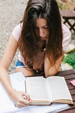 Young beautiful female sitting outside and studying hard. Stock Photo