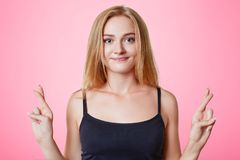 Young beautiful female student keeps fingers crossed, makes desired wish, believes in success or good luck, isolated over pink bac. Kground. Hopeful light haired Stock Photo